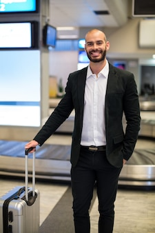 空港の待合室で荷物を持って立っているビジネスマン