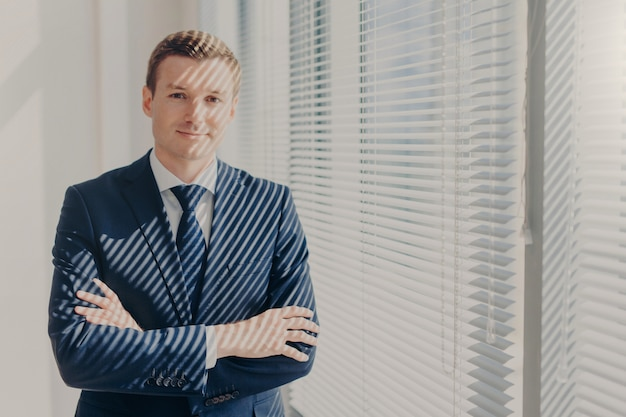 Businessman stands arms crossed near office window with jalousie