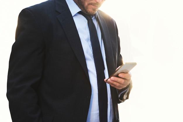 Uomo d'affari che fissa lo smartphone su sfondo bianco