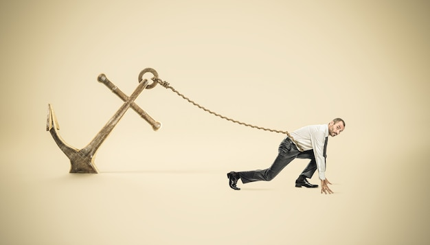 Businessman in starting position tied to a big anchor fixed to the ground.