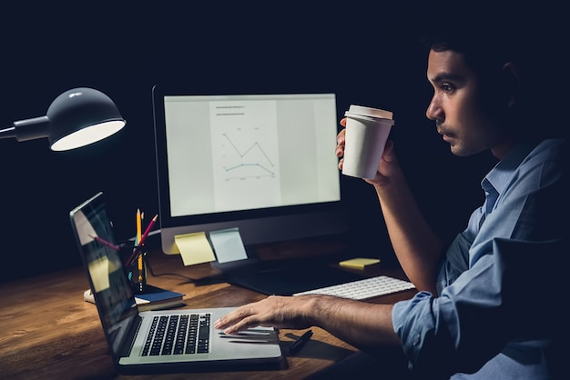 Businessman staying overtime late at night in the office focusing on working with notebook computer