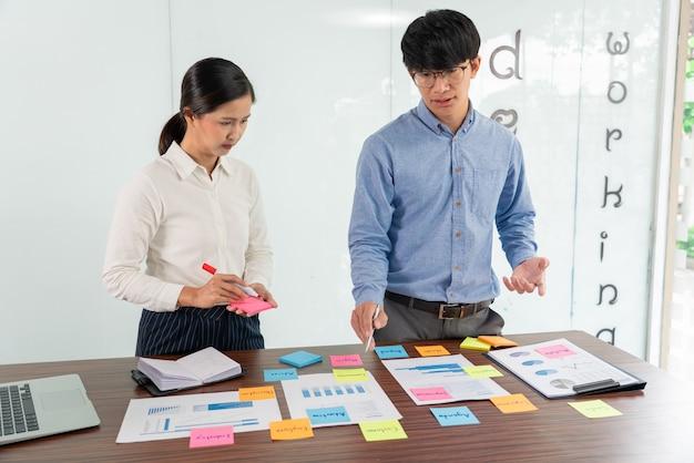 Бизнесмен наклеивает красочные заметки для мозгового штурма на столе, работая над новым проектом с коллегой