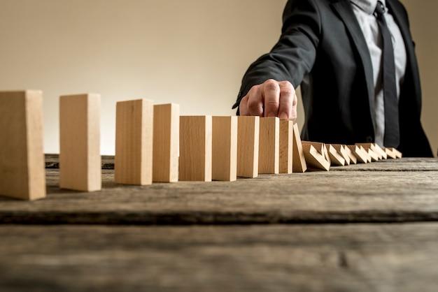 Бизнесмен останавливает эффект домино пальцем