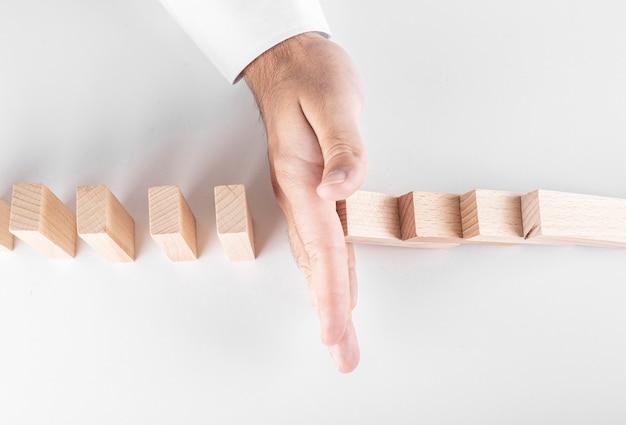 Бизнесмен, останавливающий упавшие деревянные блоки