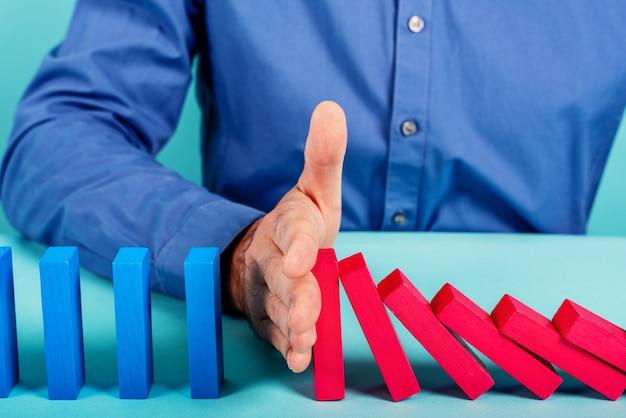 ビジネスマンはドミノゲームのおもちゃのようにチェーンの落下を停止します。ビジネスの危機と失敗を防ぐための概念