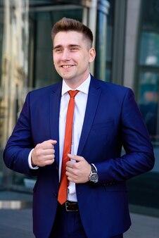 Бизнесмен поправляет галстук.