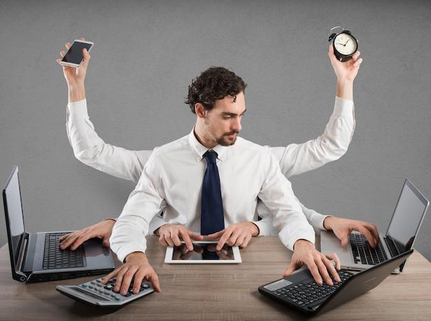 Бизнесмен, подчеркнутый слишком большим количеством задач, работает в офисе