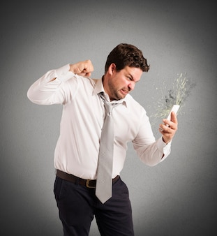 Бизнесмен, подчеркнутый на работе, ломает свой мобильный телефон