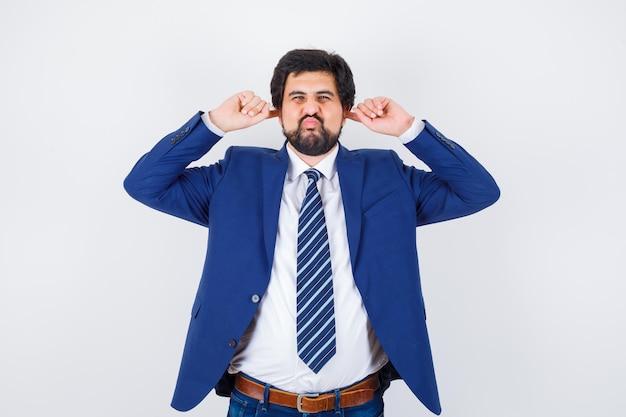 사업가 귀를 스트레칭하고 공식적인 양복에 뺨을 부풀리고 즐겁게 보입니다. 전면보기.
