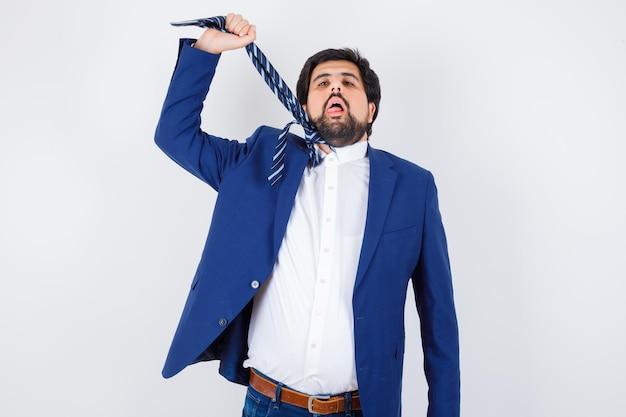 ビジネスマンはフォーマルなスーツでネクタイを伸ばし、疲れ果てた、正面図を探しています。