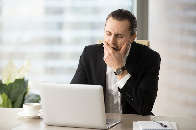 Businessman struggling with drowsiness at work