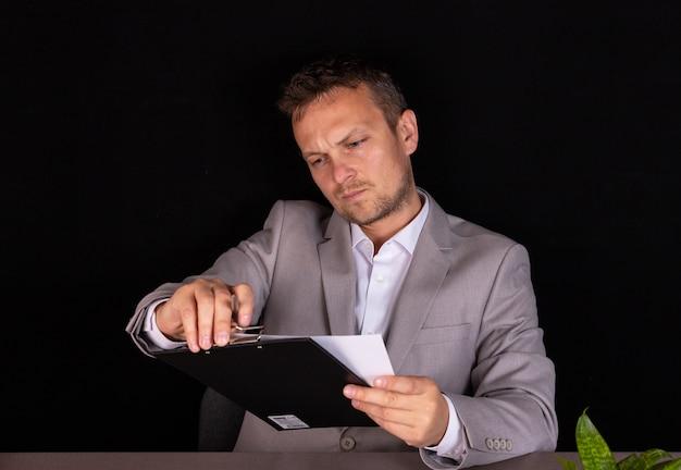 彼はオフィスの机に座って真剣な表情で紙の文書を勉強しているビジネスマン