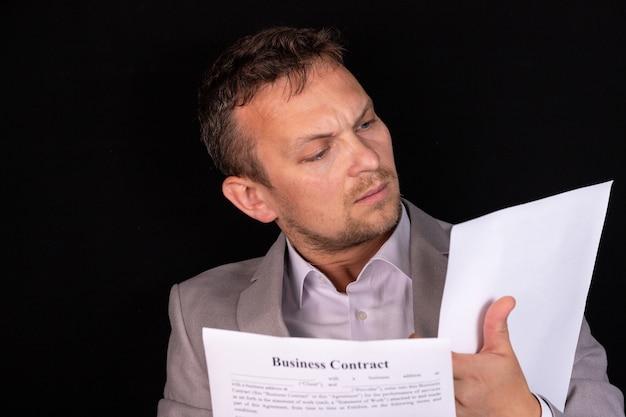 彼はオフィスの彼の机に座って真剣な表情で紙の文書を勉強しているビジネスマン