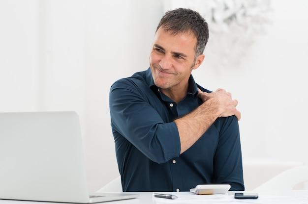어깨 통증에서 고통받는 사업가