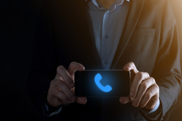Businessman in suit on black background clicks on phone icon.call now business communication support center customer service technology concept.