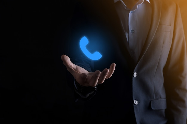 Businessman in suit on black background hold phone icon