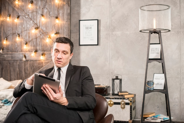 Businessman in suit browsing tablet