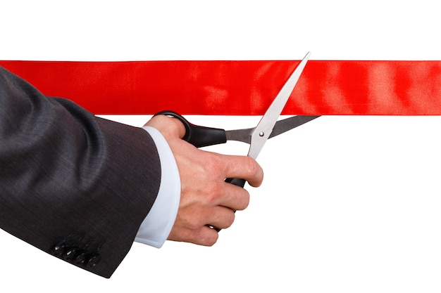 Businessman in suit cutting red ribbon with pair of scissors
