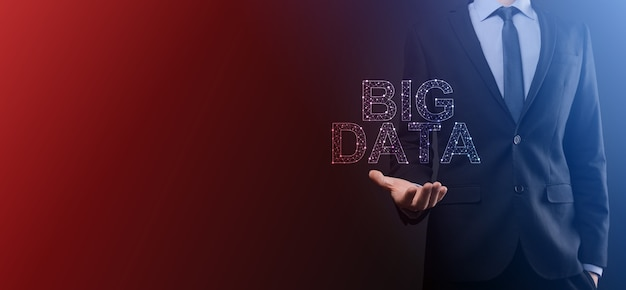 Businessman in a suit on a dark background holds the inscription big data. storage network online server concept.social network or business analytics representation.