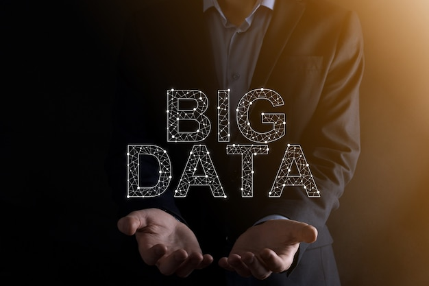 Businessman in a suit on a dark background holds the inscription big data. storage network online server concept.social network or business analytics representation