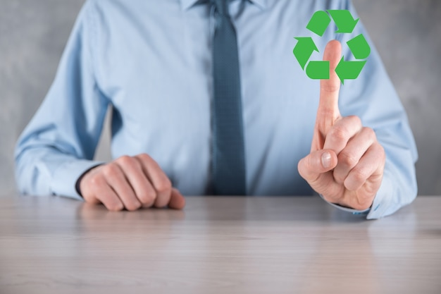 Businessman in suit over dark background holds an recycling icon, sign in his hands. ecology, environment and conservation concept. neon red blue light.