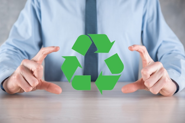 Businessman in suit over dark background holds an recycling icon, sign in his hands.
