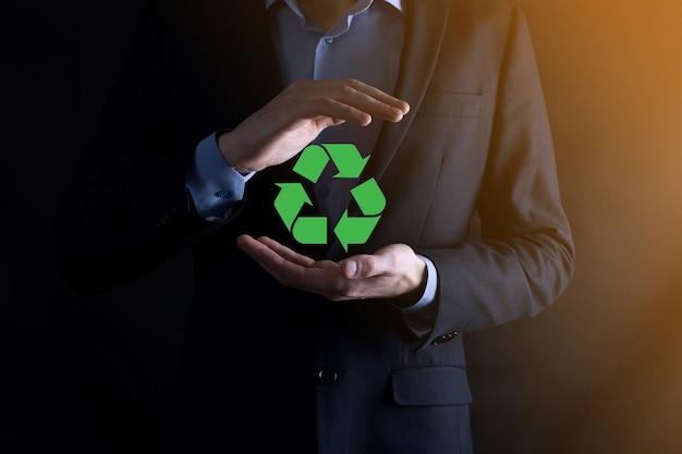 Businessman in suit over dark background holds an recycling icon