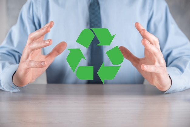 Businessman in suit over dark surface holds an recycling icon, sign in his hands