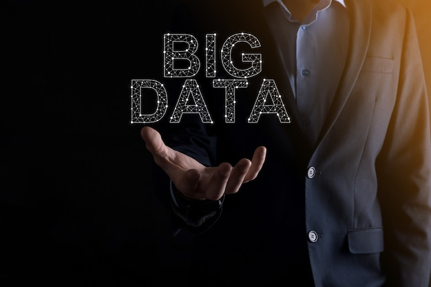 Businessman in a suit on a dark wall holds the inscription big data. storage network online server concept.social network or business analytics representation.