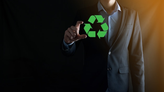 Businessman in suit over dark wall holds an recycling icon, sign in his hands. ecology, environment and conservation concept. neon red blue light.