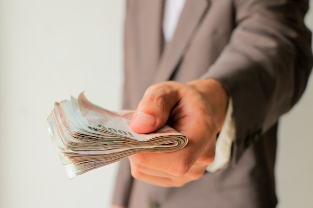 Businessman in suit giving many money