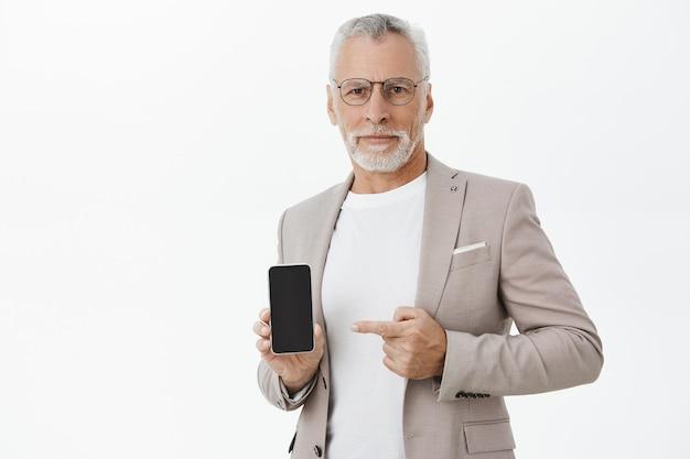 Imprenditore in tuta e occhiali puntare il dito sul display del telefono cellulare