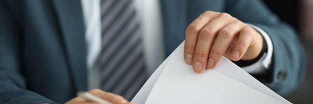 Businessman in suit holding documents in his hands in office closeup hr management concept