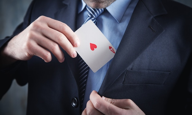 Businessman in suit holding playing card.