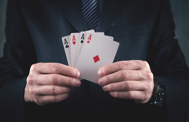 Businessman in suit holding playing cards.