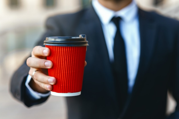 Businessman in a suit holding a red paper cup of coffee in his hands to take away.  mockup