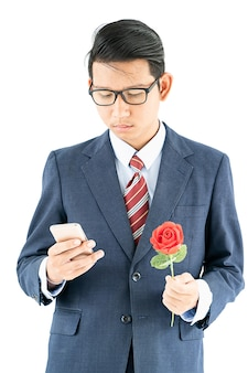 Businessman in suit holding smartphone and red rose