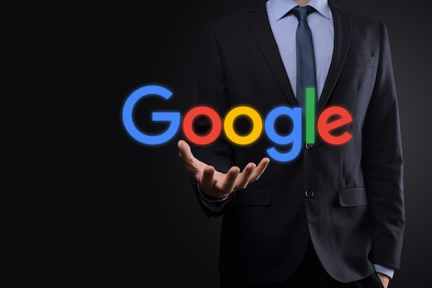 Businessman in a suit holds a google logo
