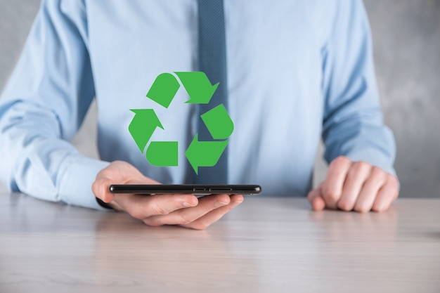 Businessman in suit holds an recycling icon sign in his hands
