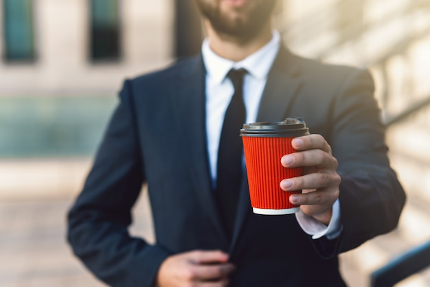 Businessman in a suit holds a red paper cup of coffee in his hands to take away. mockup