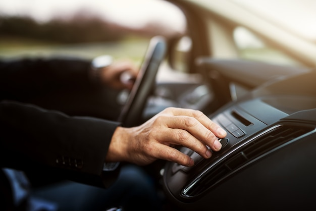 Businessman in suit is adjusting a volume on his stereo while driving a car.