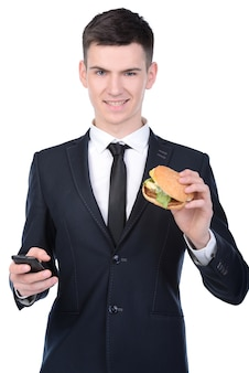 Businessman in suit is eating hamburger.