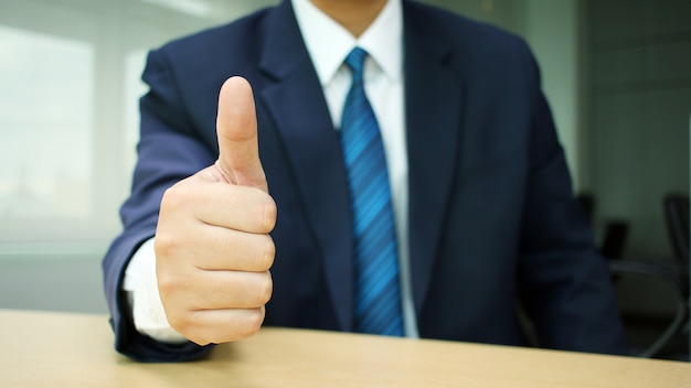 Businessman in suit lifts his hand make the superb sign at desk