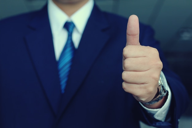 Businessman in suit lifts his hand make the superb sign