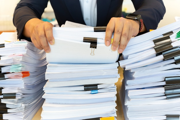 Businessman in suit look through pile of documents in office.