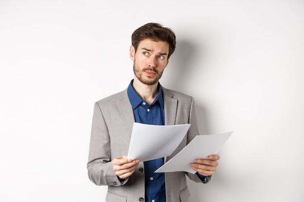 Businessman in suit looking through papers, reading documents at work and thinking, looking aside at logo, standing busy on white background.
