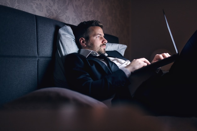 Businessman in suit lying in the bed in hotel room and using laptop for work. overworking concept.