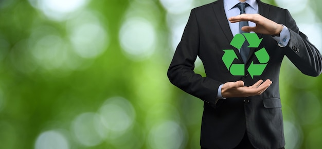Businessman in suit over natural green background holds an recycling icon, sign in his hands.