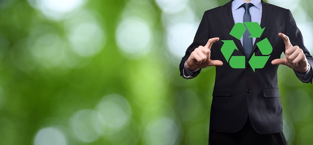 Businessman in suit over natural green background holds an recycling icon, sign in his hands