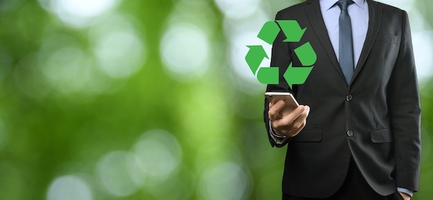 Businessman in suit over natural green background holds an recycling icon